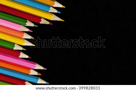 Colored pencils set on a black background - stock photo
