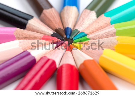 colored pencils stacked in a circle over white
