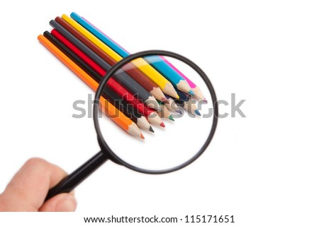 Colored pencils under the magnifying glass - stock photo