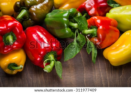Colored Peppers on a wooden surface. - stock photo