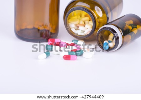 Colored pills and tablets on white background - stock photo