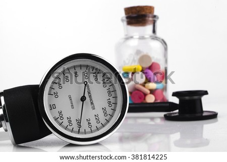 Colored Pills in a Jar with Sphygmomanometer and Black Stethoscope - stock photo