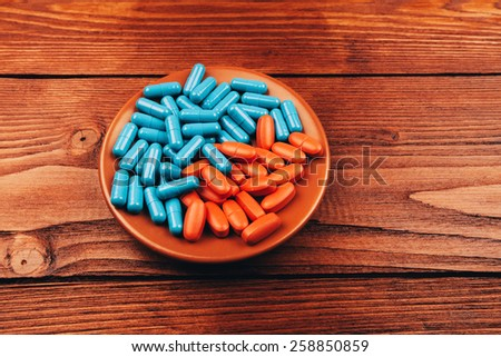 Colored pills lying on wooden table - stock photo
