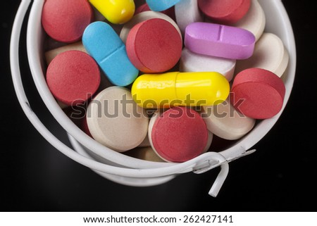 Colored pills medicine in a white bucket close-up on black background - stock photo