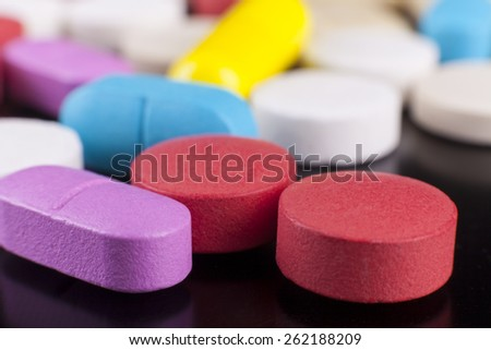 Colored pills medicine macro close-up on black background - stock photo