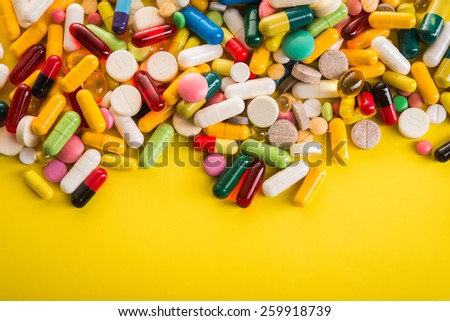 Colored pills on yellow background. Top view. - stock photo