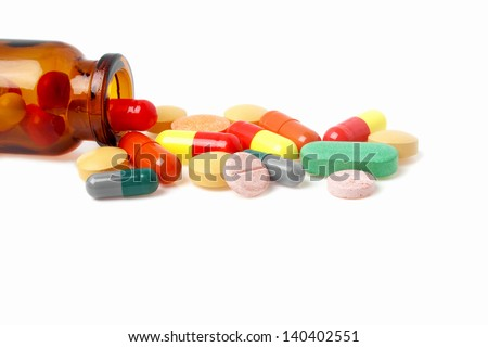 Colored pills, tablets and medicine bottle on a white background