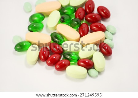 Colored pills, tablets and soft gel capsules on a white background - stock photo