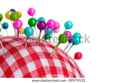 Colored pinheads in pin-cushion isolated on white - stock photo