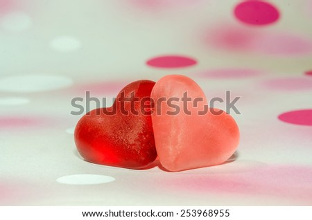 Colored (pink, red and orange), transparent heart shape jellies, close up, pink bokeh background. - stock photo