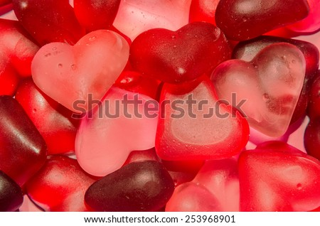 Colored (pink, red and orange), transparent heart shape jellies, close up, texture. - stock photo