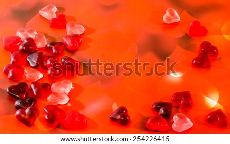 Colored (pink, red and orange), transparent heart shape jellies, red hearts background. - stock photo