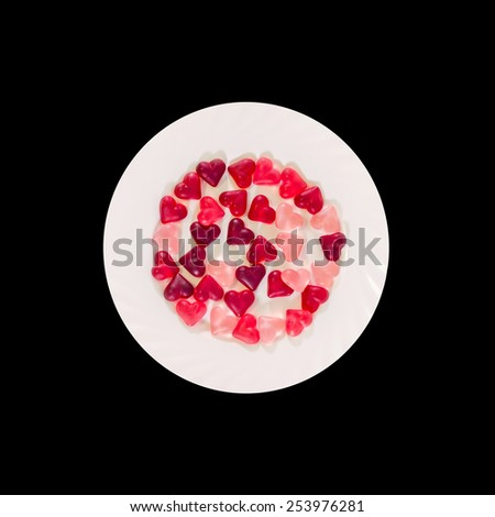 Colored (pink, red and orange), transparent heart shape jellies with ceramic plate, black background, isolated. - stock photo
