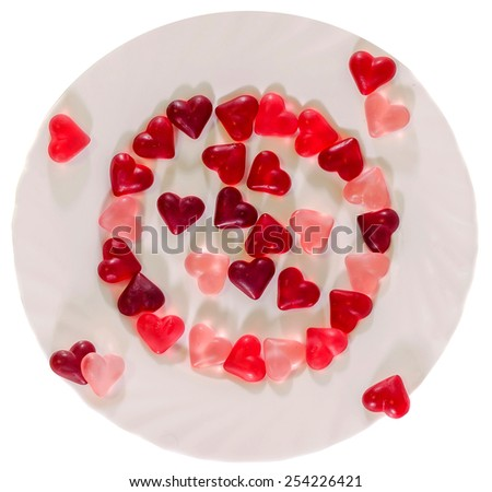 Colored (pink, red and orange), transparent heart shape jellies with ceramic plate, white background, isolated. - stock photo