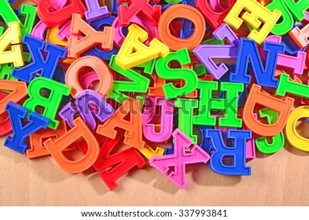 Colored plastic alphabet letters on a wooden background