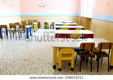 colored plastic chairs and small tables of the refectory in early childhood school - stock photo