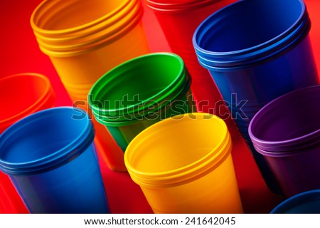 Colored plastic glasses on red background