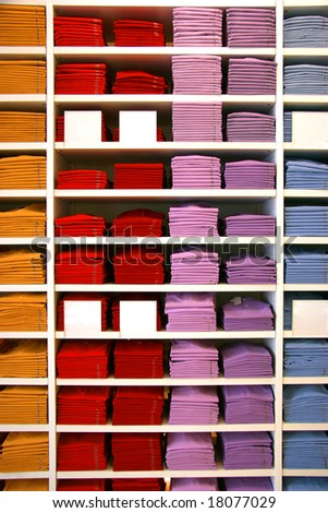 Colored polo shirts on display in a shop. Blank description tags. - stock photo