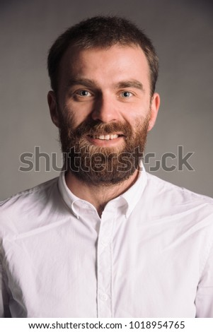 Colored portrait of smiling man with beard in white shirt isolated on gray studio background posing to the camera