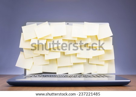 Colored post-it notes covering laptop screen - stock photo