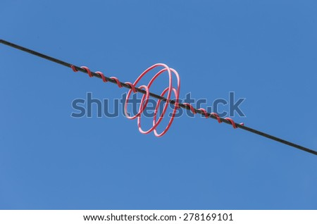 Colored protective spiral mounted on the cable high voltage power lines. - stock photo