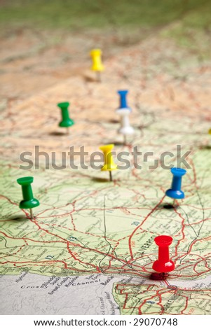 Colored pushpins on a road map of a tourist - stock photo