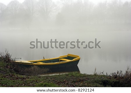 Colored river boat in the border of Lima river in a misty day (Ponte de Lima, Portugal) - stock photo
