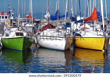 Colored sail boats parked on the dock of a lake. Yellow, green, white, color reflections on water. - stock photo