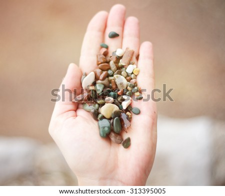 colored sea pebbles in the palm of your hand - stock photo