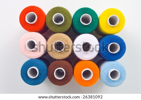 colored sewing spools on white background
