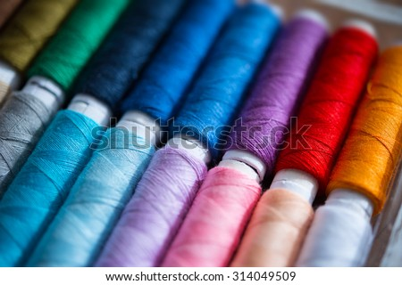 Colored sewing threads. Focus on purple thread. Shallow depth of field. - stock photo