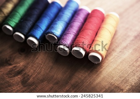 Colored sewing threads on a old work table with impressional feel. - stock photo