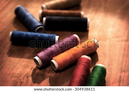 Colored sewing threads on a old work table with impressional tone and feel. Shallow depth of field. - stock photo