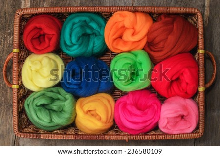 colored skeins of wool felting in a wicker tray
