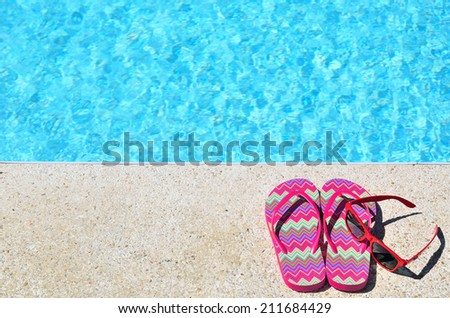 Colored slipper and sunglasses beside the blue pool -- Summer holidays concept  - stock photo