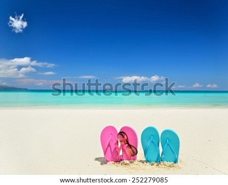 Colored slippers and sunglasses at the tropical beach -- Concept of tropical vacation  - stock photo