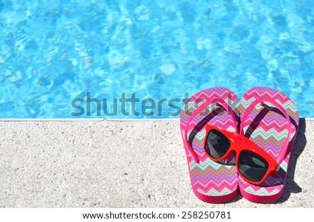 Colored slippers and sunglasses beside swimming pool  - stock photo