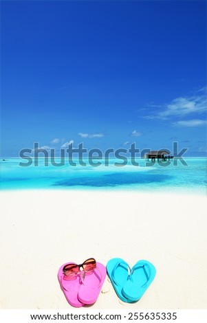 Colored slippers at the tropical beach -- Tropical beach vacation and travel concept   - stock photo