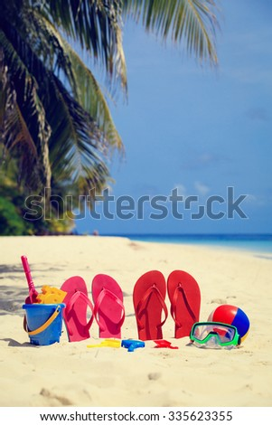 Colored slippers, toys and diving mask at beach, vacation concept - stock photo