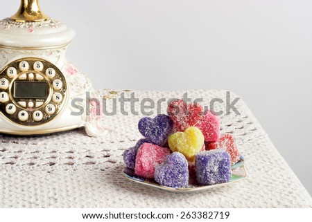 colored soap in the form of heart on a white crocheted tablecloth - stock photo