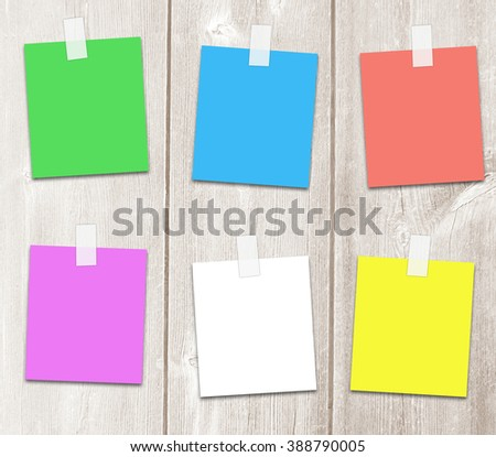 Colored sticker paper on adhesive tape with copy space for text, notes,announcements on a light wooden background boards.
