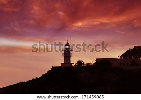 Colored sunset in the coast linea and lighthouse with light stream - stock photo