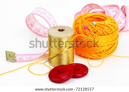 Colored thread, needles and buttons on a white background - stock photo