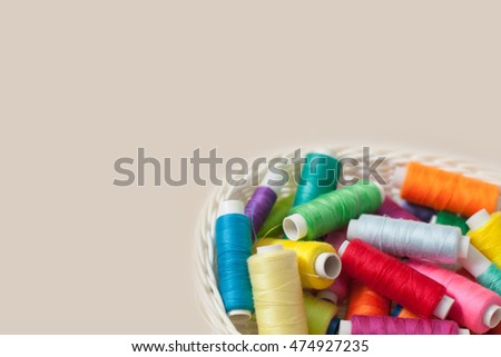 Colored threads for sewing on a beige background. White basket with threads.