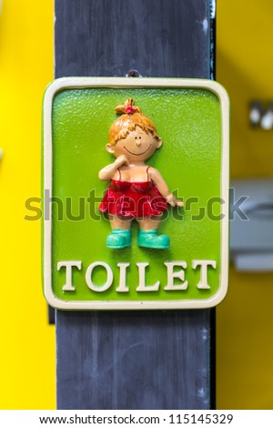 Colored toilet symbol on wooden post. - stock photo