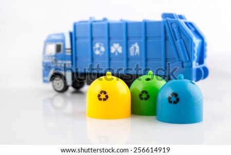 Colored trash bins and garbage truck toys on white background - stock photo