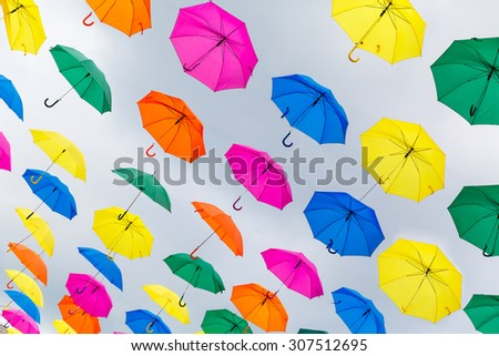 colored umbrellas on the background an overcast sky - stock photo