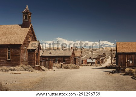 Colored vintage old looking photo of empty streets of abandoned ghost town Bodie in California, USA in the middle of a day. - stock photo