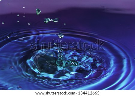 Colored water droplets collisions macro..  Closeup of multiple green water droplets gall into blue and purple water. - stock photo