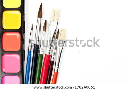Colored watercolor paint set with multicolored brushes isolated on white background with space for your text